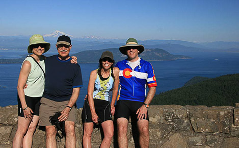 Guests on a biking tour of Orcas Island take a photo in front of Mount Baker